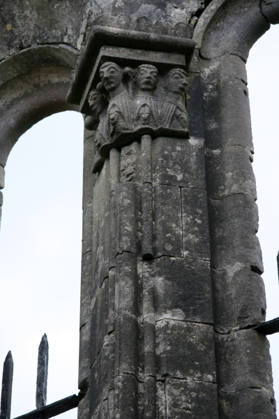 Some praying clerics at the top of a column.