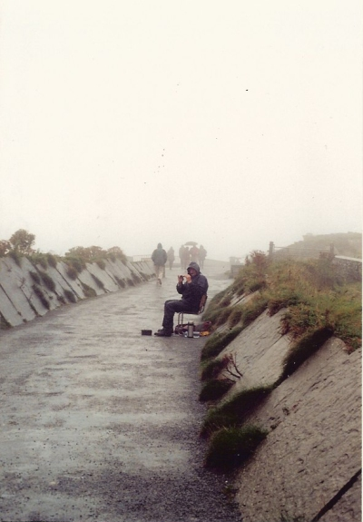 The approach to the cliffs in 2003. A short railing was all that stood between visitors and the sea (once you'd turned right or left, the walk along the cliff was virtually unimpeded, except for the warning signs). That's a busker playing a tin whistle, with the entrance to the gift shack just beyond him to the right.