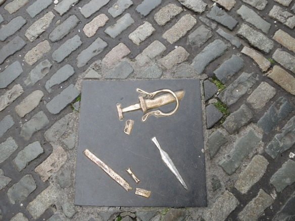 There's a narrow alley on the far side (north). This little exhibits is embedded in the cobblestones. No plaque. Interesting, old … important enough to preserve (sort of!) but maybe not historically important. (Margaret's photo.)