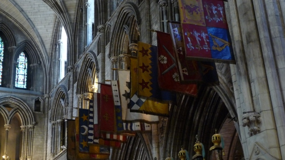 """Flags up closer. The cathedral guidebook says England's """"King George III founded the Most Illustrious Order of St. Patrick in 1783. … Each knight had his banner, symbolic sword, helmet, and crest placed over his stall in the choir."""" You can see some of the helmets in the lower part of the photo."""