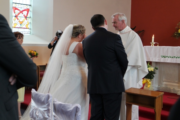 The bride joins her groom in front of the altar. I don't know what Father Jones said but it was an emotional moment.