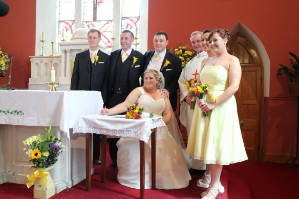 This is something that happens at Irish Catholic weddings (the only kind I've been to): the signing and witnessing of the marriage certificate is actually a part of the ceremony. And then they pause for everyone to take pictures.