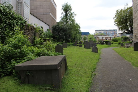 The churchyard, taken on the other side of the church, with a different towering office building.