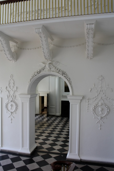 I'm standing on the stairs, looking through the doorway into the foyer or entry hall. Just look at that plasterwork.