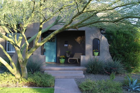There is nothing I don't love about this—the shady front porch, that aqua front door, the way the palo verde tree both frames the entrance and mimics the curving lines of the side wall, the way the apple green pots echo the bark on the green tree, the way the marigolds pop. Gosh, this is just gorgeous.