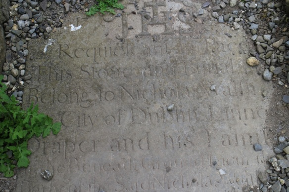 This gravestone was laid in the 1700s (see upper left corner), though it probably stood upright then. This is what I could read: Requiescat in Pace / This stone and burial *** / Belong to Nicholas Walsh / City of Dublin Linne** / Draper and his Family.