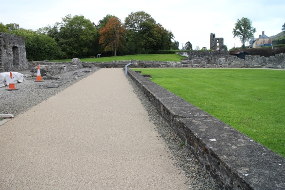 What was once gravel is now paved. The cloister is to the right, the barely there church is straight ahead, miscellaneous buildings on the left. Far in the distance, the towering remains of the original gatehouse of the old abbey. The entrance road formerly led through the archway beneath the tower.