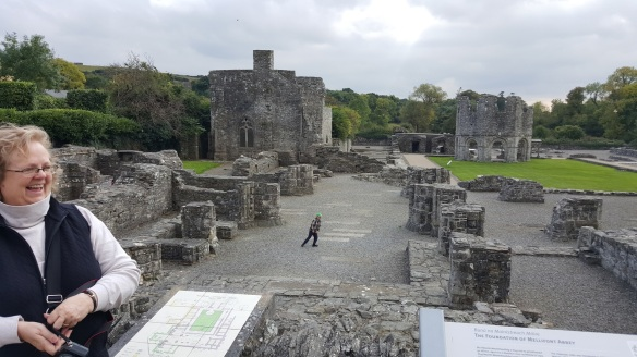 In the foreground, all that remains of the great cruciform church. On the left, the chapter house, which would have been adjacent to the church. The grassy area in the center is the cloister, on which sits the original lavabo. I'm standing next to a site map. (John took this photo.)