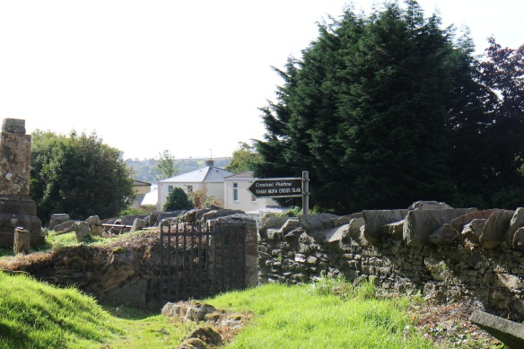Entrance to the ruined graveyard, with the sign pointing to the oldest cross, said to be St. Mura's headstone.
