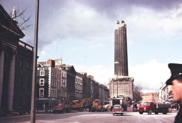 """A half-demolished Nelson's Pillar on O'Connell Street, Dublin. From the front page of the Irish Times on Tuesday, 8 March 1966: """"The top of Nelson Pillar, in O'Connell street, Dublin, was blown off by a tremendous explosion at 1.32 o'clock this morning and the Nelson statue and tons of rubble poured down into the roadway. By a miracle, nobody was injured, though there were a number of people in the area at the time."""" Date: Tuesday, 8 March 1966 Source: The National Library of Ireland/Flickr"""